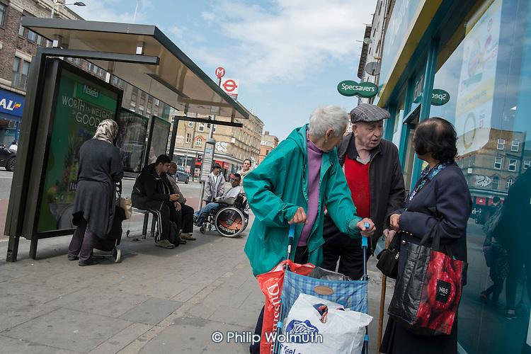 Elderly shoppers chat outside a Poundland store, Kilburn, London.