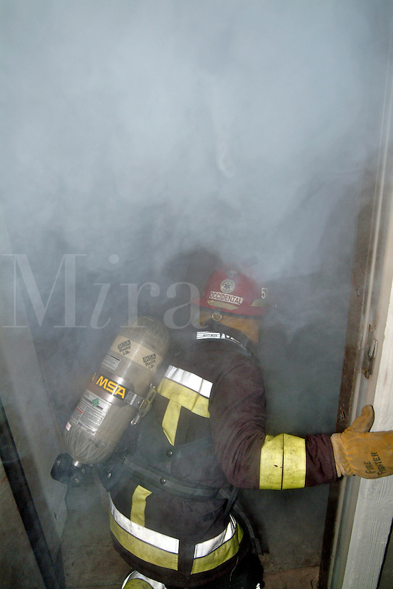 A firefighter prepares to enter a smoke filled building.  Smoke training inside the fire house of the Occidental Volunteer Fire Department using a smoke machine with all of the fire engines removed.