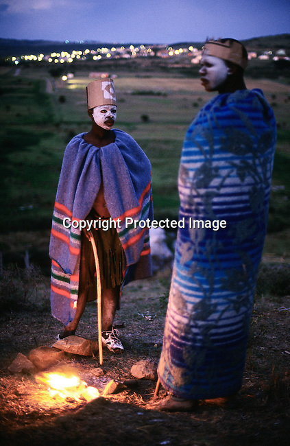 Unidentified Xhosa boys keep warm at a fire as they are going trough a traditional manhood ceremony on August 20, 2000 in Tshatshu, in the Eastern Cape Province in South Africa. The ceremony lasts for about six weeks starting with a circumcision. The wound has to be healed in a natural way, and traditional healers and elders guide the boys during the ceremony, which is to prepare them for adulthood. Former South African president Nelson Mandela went trough the ceremony when he was young. (Photo by: Per-Anders Pettersson).