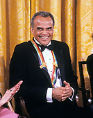 Singer and actor Harry Belafonte listens as first lady Barbara Bush makes remarks during a ceremony for 1989 Kennedy Center Honorees in the East Room of the White House, December 3, 1989 in Washington, DC. The 1989 honorees are: actress and singer Mary Martin, dancer Alexandra Danilova, singer and actor Harry Belafonte, actress Claudette Colbert, and composer William Schuman.<br /> Credit: Peter Heimsath / Pool via CNP