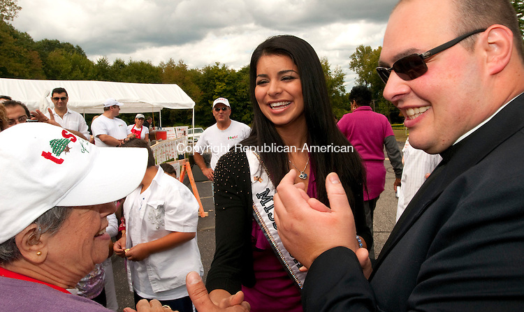 WATERBURY, CT, 18 SEPTEMBER, 2010-091810JS15-Rima Fakih, Miss USA 2010, center, shares a laugh with Lorette Stevens of Waetrbury, left, and Father Maji Kiwan, the parish priest at Our Lady of Lebanon Maronite Catholic Church, during her visit to the 11th annual Taste of Lebanon Festival on Saturday at Ceders Hall on East Mountian Road in Waterbury. Rima Fakih, who was crowned Miss USA in May, was born in Lebanon. The festival continues today following a 10 a.m. Mass until 7 p.m.<br /> Jim Shannon Republican-American