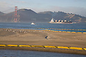 Oil spill containment booms (yellow) line the sands and waters of Crissy Field as a container ship enters San Francisco Bay (11/12/07). On November 7, 2007 the Cosco Busan container ship spilled an estimated 58,000 gallons of bunker fuel into San Francisco Bay after striking a tower of the San Francisco-Oakland Bay Bridge.