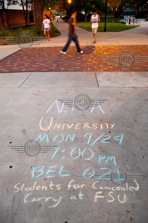 A sign on the pavement in chalk, at the Florida State University campus, advertises a meeting sponsored by the NRA (National Rifle Association, America's powerful pro-gun lobby). The meeting is in support of 'Students for Concealed Carry at FSU' (for students to be allowed to carry concealed weapons on campus). Florida already has some of the most lenient gun regulations in the country. Ordinary citizens are allowed to carry concealed weapons on their person but, up to now, it is still prohibited to carry guns at schools and Universities. The US Presidential election will be held on 6 November, 2012.