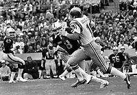 Oakland Raiders Monte Johnson chasing SDan Diego quarterback Bobby Douglas..(1975 photo/Ron Riesterer)