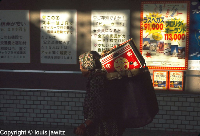 Train station Japan  Senior  old lady carrying Cardboard Box on back ,back pack