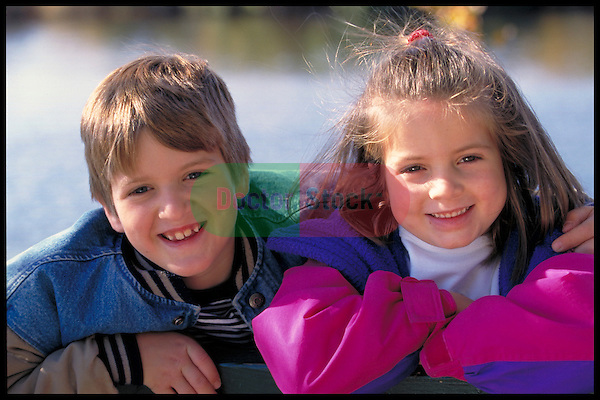 portrait of smiling young boy and girl in park