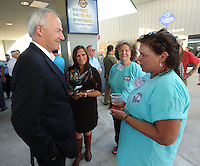 NWA Democrat-Gazette/ANDY SHUPE<br /> Gov. Asa Hutchinson (left) speaks Thursday, Sept. 17, 2015, with Denise Bembenek, events coordinator with Soldier ON Service Dogs, Inc., during the fifth annual Chickin, Peelin' & Politickin' at Arvest Ballpark in Springdale. Regional civic and business leaders have the opportunity to speak with national, state, regional and local political leaders and elected officials at the event, which is organized by the Springdale Chamber of Commerce.