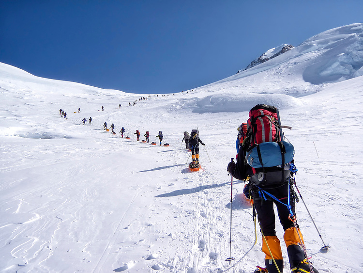 After a 5 day wind storm in camp 2 on the West Buttress route on Denali, everyone is anxious to climb to camp 3 up Motorcycle Hill on a beautiful day. The winds have scoured the snow down to a firm layer as climbers carry heavy loads with sleds full of gear.