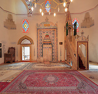 Prayer hall of the Koski Mehmed Pasha mosque, built 1618, in Mostar, Bosnia and Herzegovina, with decorative mihrab on the wall and minbar on the right. The town is named after the mostari or bridge keepers of the Stari Most or Old Bridge. Mostar developed in the 15th and 16th centuries as an Ottoman frontier town and is listed as a UNESCO World Heritage Site. Picture by Manuel Cohen