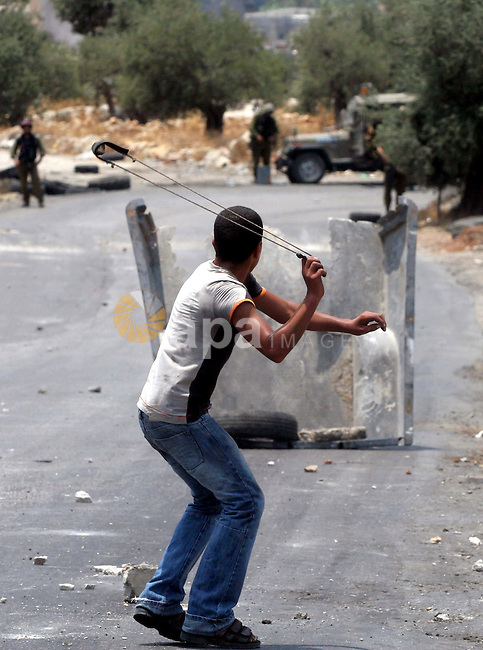 Palestinian youths hurl stones at Israeli soldiers during a demonstration against the construction of the controversial Israeli cement barrier in the West Bank village of Nilin near Ramallah.