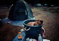 Young girl stays warm ducking into a bucket of warm water while taking a bath in the camp ground at Yosemite National Park. Her mother was getting a towel out of the tent to dry her off.