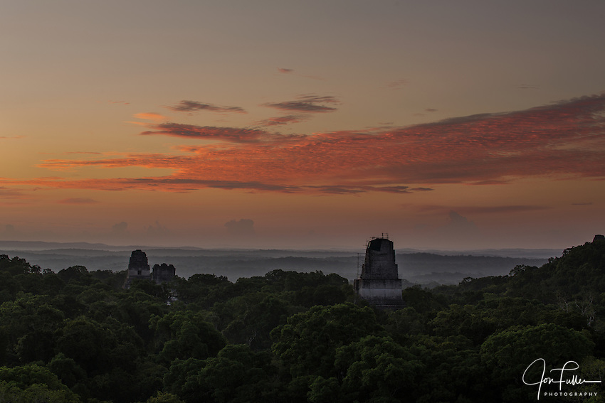 Predawn view of Temples I, II and III from Temple IV in the Mayan archeological site of Tikal National Park, Guatemala.  A UNESCO World Heritage site since 1979.  Scaffolding for the ongoing stabilization work is present on Temple III.