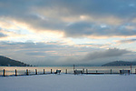 Fresh snow on a December dawn.  Cables and posts covered in snow guard the edge of the North Idaho College dike on Lake Coeur D Alene, Idaho.