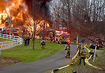 Firefighters pull hoses as a massive fire consumes a large home on Barber Hill Road that completely  destroyed the home, Thursday evening, April 11, 2019, in East Windsor. (Jim Michaud / Journal Inquirer)