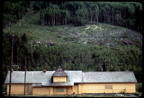 A town-side view of RGS Telluride depot following abandonment.  Building is boarded-up, awaiting reuse.  Ski area development taking place on hillside behind depot.<br /> RGS  Telluride, CO  Taken by Maxwell, John W. - 6/27/1965