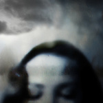 top half of a woman's head with eyes closed and clouds in the background