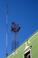 Building facade and radio tower on the roof in the Zocalo in Campeche, Mexico.
