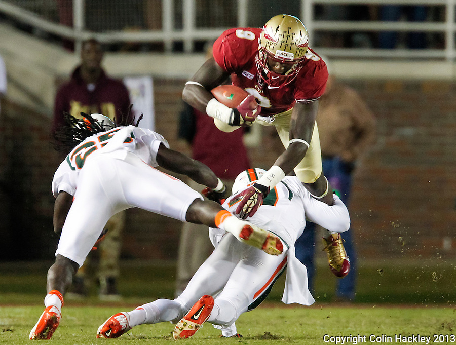 TALLAHASSEE, FL 11/2/13-FSU-MIAMI110213CH-Florida State's Karlos Williams is tackled on a kickoff return by Miami's Antonio Crawford as Dallas Crawford, left, flies by during first half action Saturday at Doak Campbell Stadium in Tallahassee. <br /> COLIN HACKLEY PHOTO