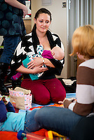 "A mother breastfeeds her baby while talking to another mother at a drop-in breastfeeding support centre.<br /> <br /> Image from the breastfeeding collection of the ""We Do It In Public"" documentary photography picture library project: <br />  www.breastfeedinginpublic.co.uk<br /> <br /> Hampshire, England, UK<br /> 13/03/2013<br /> <br /> © Paul Carter / wdiip.co.uk"