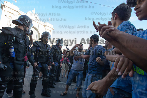 Illegal migrants face a line of riot police as they protest against the circumstances at the transit zone they are kept in at the main railway station Keleti in Budapest, Hungary on September 02, 2015. ATTILA VOLGYI