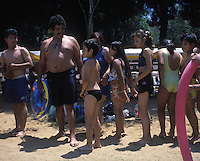 Waiting in line to take a shower before entering the pools at one of 4 Urban beaches recently inaugarated in Mexico City, as many as the beaches consist of swimming pools, 120 tons of sand, volleyball courts, industrial fans to mimic the wind, they are free and enourmously popular, as many as 4000 people (although designed for 3000) line up early in the morning to enjoy its instalations.  Villa Olimpica, Mexico City, Easter Sunday, April 8, 2007