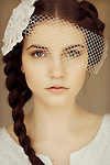 Close portrait of young woman with bridal headpiece and braided hair looking straight forward