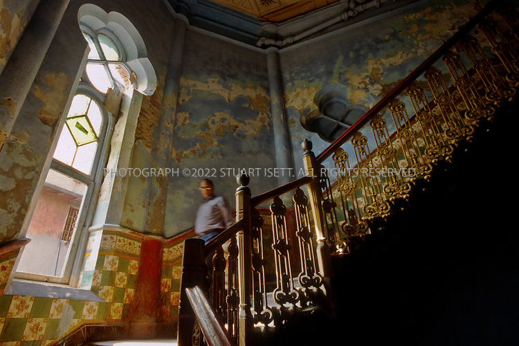 "12/1/2006--Kolkata (Calcutta), India..Main staircase in the Tagore Castle on P.K. Tagore Street. The building has been heavily modified and only bare traces of its past now remain. The influence of European style architecture can be seen in the house of Jatindra Mohan Tagore. Called ""Tagore Castle"", this house (built between 1800 and 1850) looks like a castle, complete with turrets right in the heart of the city. The building has been heavily modified to become an almost 'Frankenstein' building and only bare traces of its past now remain and is occupied by dozens of different tenants...The Tagore's were major patrons of European art and this palatial home, the Tagore Castle, had a major collection of European paintings.  The Tagore family, with over three hundred years of history, has been one of the leading families of Kolkata, and is regarded as a key influence during the Bengal Renaissance. ..Photograph By Stuart Isett.All photographs ©2006 Stuart Isett.All rights reserved."