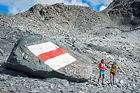 A giant Swiss Wanderweg trail sign on a rock during the Via Valais, a multi-day trail running tour connecting Verbier with Zermatt, Switzerland.