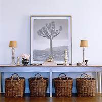 A series of wicker baskets is lined up underneath the long console table in the entrance hall which displays a large framed photograph, small sculptures, antique candlesticks and a pair of matching table lamps