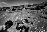 KHAK-E-JABAR DISTRICT, AFGHANISTAN - MAY 15. .Eight-year-old Zahedullah drinks water after a long day collecting scrap metal outside his village in Khak-e-Jabar district. The areas in and around the capital Kabul were heavily mined during the Soviet invasion of Afghanistan in the 1980's. Many children such as Zahedullah collect shrapnel in order to sell as scrap metal - it is not uncommon that these children get maimed of killed by land mines they encounter while trying to make a living collecting scrap metal. (Javier Manzano / For The Washington Post). ..