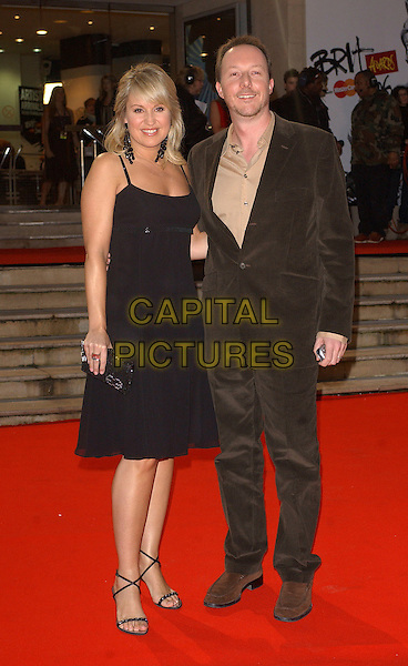 NIKKI CHAPMAN & GUEST.The 2006 Brit Awards with Mastercard at Earls Court, London, UK..February 15th 2006.Ref: BEL.brits full length black dress brown suit.www.capitalpictures.com.sales@capitalpictures.com.© Capital Pictures.