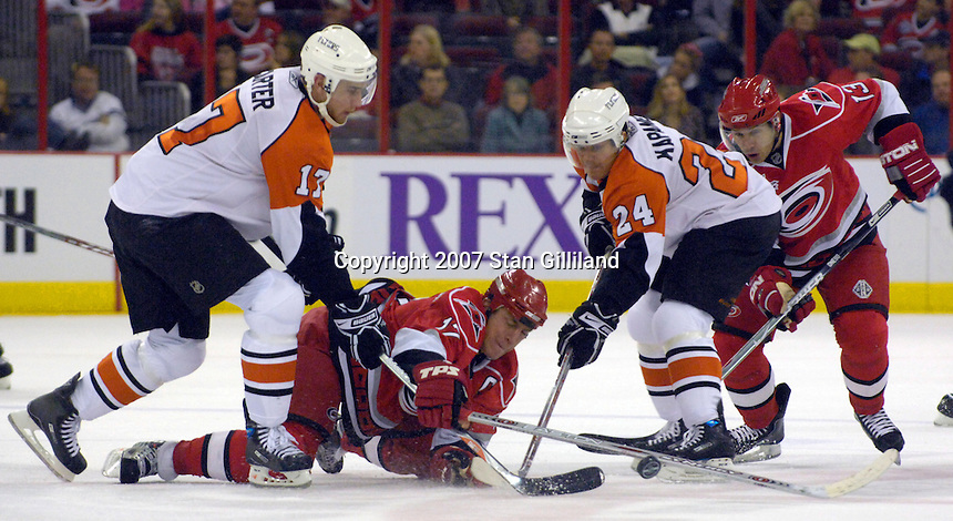 The Carolina Hurricanes' captain Rod Brind'Amour (17) reaches for a puck defended by the Philadelphia Flyers' Sami Kapanen (24) and Jeff Carter (17) Wednesday, Nov. 21, 2007 in Raleigh, NC. The Flyers won 6-3.
