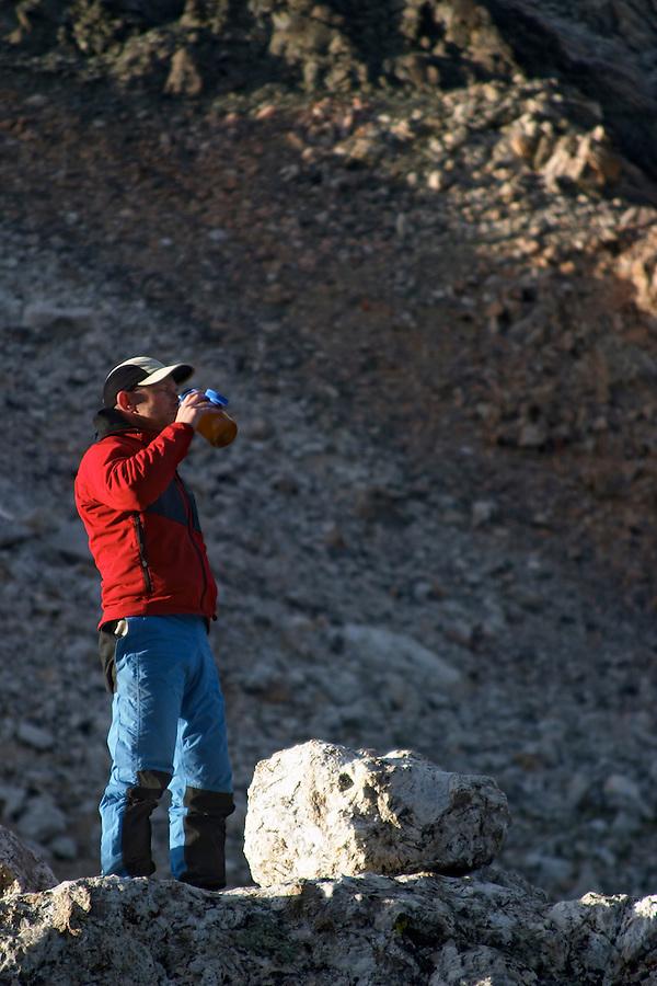 Man standing beside boulder drinking from water, Grand Teton Lower Saddle, Grand Teton National Park, Teton County, Wyoming, USA