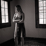 Woman standing in empty dark room with arms folded