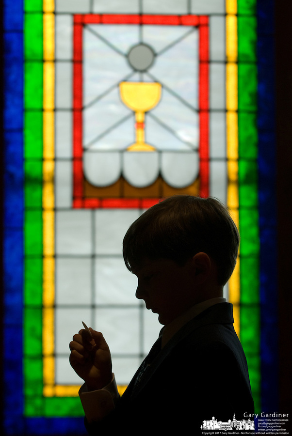 Young boy holds communion wafer at his first communion in the Catholic church.