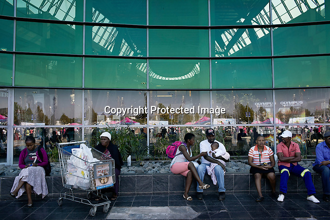 SOWETO, SOUTH AFRICA MAY 1: Shoppers relax outside a mall on May 1, 2013 at Maponya shopping Mall, Soweto, South Africa.  Maponya is one of several new shopping malls in the township. Soweto today is a mix of old housing and newly constructed townhouses. The population in Soweto is estimated to be around one million people. A new hungry black middle-class is growing steadily. Many residents work in Johannesburg but the last years many shopping malls have been built, and people are starting to spend their money in Soweto. (Photo by: Per-Anders Pettersson)