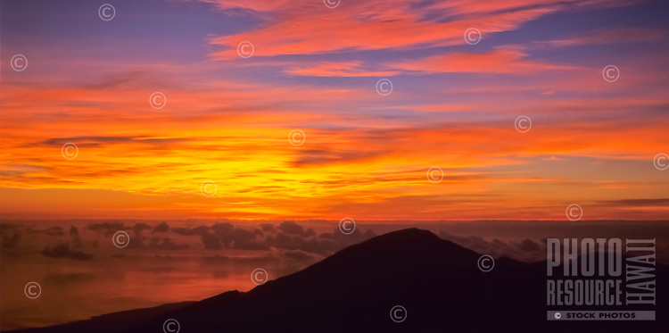 A rare image of the colors of a Haleakala sunrise being reflected in the ocean below. This photo was taken from atop Mt. Haleakala, seen in the foreground, in Haleakala National Park, Maui.
