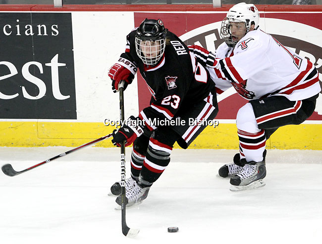 St. Cloud State's Cam Reid controls the puck while being pressured by UNO's Joey Martin. UNO beat St. Cloud State 3-0 Friday night at Qwest Center Omaha.  (Photo by Michelle Bishop)