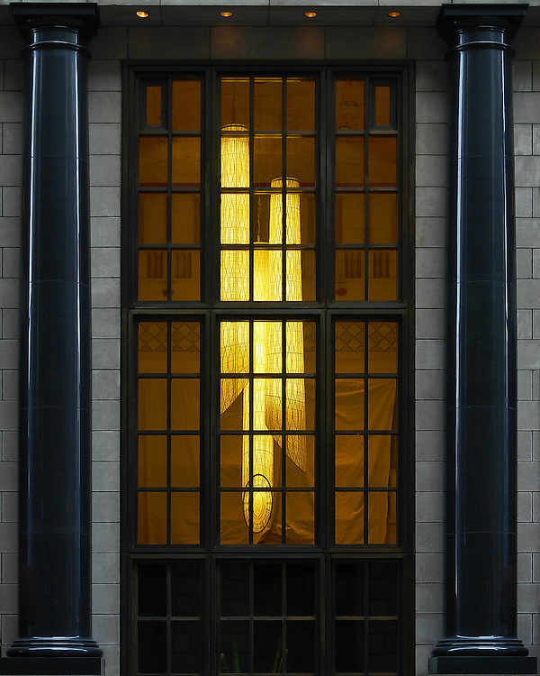 A multi-paned window, framed by two polished black columns, through which three very long lantern-like lights, hung from a high ceiling, glow in the diminishing light of the evenng.
