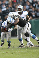 December 18, 2011 Oakland, CA: Oakland Raiders defensive end Lamarr Houston #99 and Detroit Lions running back Kevin Smith #30 during an NFL game played between the Oakland Raiders and the Detroit Lions at O.co Coliseum. The Lions defeated the Raiders 28-27.