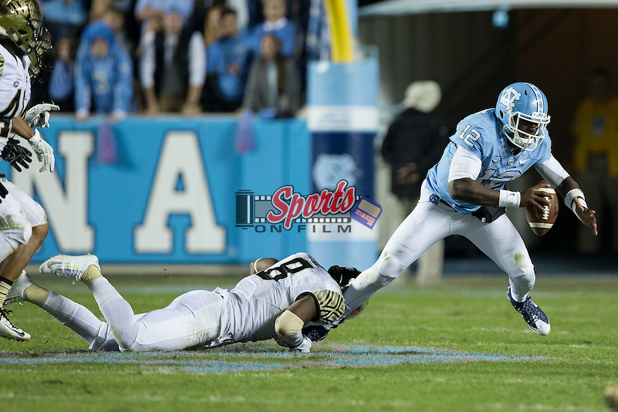 Marquise Williams (12) of the North Carolina Tar Heels is tripped up by Marquel Lee (8) of the Wake Forest Demon Deacons during second half action at Keenan Stadium on October 17, 2015 in Chapel Hill, North Carolina.  The Tar Heels defeated the Demon Deacons 50-14.   (Brian Westerholt/Sports On Film)
