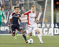 Toronto FC defender Richard Eckersley (27) works to clear ball as New England Revolution midfielder Diego Fagundez (14) closes. In a Major League Soccer (MLS) match, Toronto FC (white/red) defeated the New England Revolution (blue), 1-0, at Gillette Stadium on August 4, 2013.
