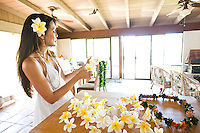 Young Hawaiian woman making a plumeria lei