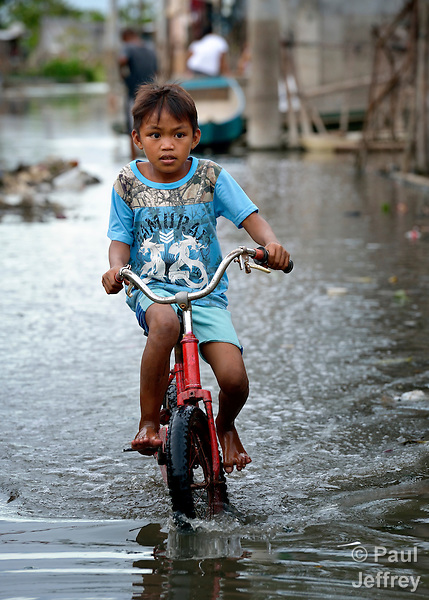 A boy rides his bicycle along a flooded street in Biñan, Laguna, in the Philippines. Residents here have been subjected to increased flooding from the Laguna de Bay in recent years, and with the help of the ACT Alliance are organizing to look for alternatives.