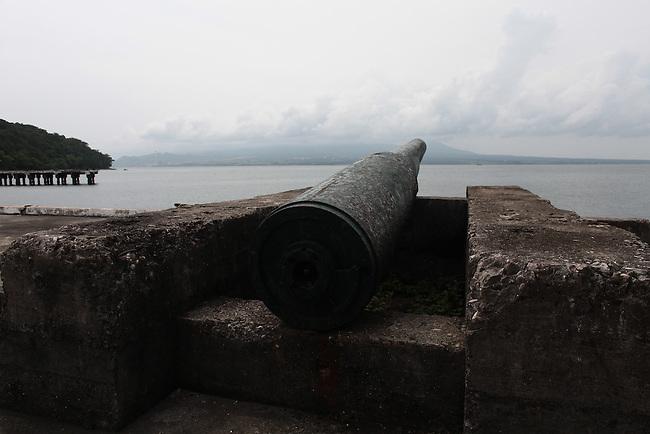 The barrel from a long unused coastal defense artillery battery points towards the Bataan Peninsula from Corregidor island, the Philippines.  June 26, 2011.