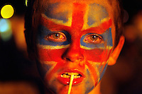 A boy with the union Jack painted on his face watches as the Irish flag is burned on a giant bonfire made from pallets and old tyres on a Loyalist estate, Belfast Northern Ireland.The bonfires which are seen by the Protestant community as a celebration of loyalist culture in the province are lit on the eve of 12 July, which is the anniversary of the Battle of the Boyne at which the Protestant King William of Orange defeated the Catholic King James in 1690. The festival causes outrage in the nearby republician and Catholic areas of the city.