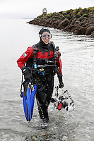 TA46756-D. female scuba diver (model released) in a drysuit and carrying an underwater camera exits the water after a fun shore dive at the Keystone Jetty in Fort Casey State Park on Whidbey Island, a short drive from Seattle. The rock breakwater behind provides habitat for a wide variety of fish and invertebrates. Bathed by nutrient rich currents, this  site is best dived at slack tide and is a favorite for scuba training, underwater photography, and critter watching. Washington, USA, Pacific Ocean.<br /> Photo Copyright &copy; Brandon Cole. All rights reserved worldwide.  www.brandoncole.com