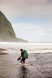USA, Hawaii, The Big Island, backpacker walks on the beach along the surf in the Waipio Valley