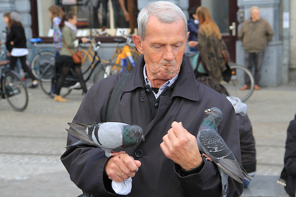 Man feeding pigeons at Dam Square, Amsterdam, Netherlands .  John offers private photo tours in Denver, Boulder and throughout Colorado, USA.  Year-round. .  John offers private photo tours in Denver, Boulder and throughout Colorado. Year-round.