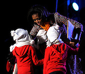 """First Lady Michelle Obama hugs children after reading """"The Night Before Christmas"""" with Kermit the Frog during the 2011 National Christmas Tree Lighting on the Ellipse in Washington, DC, on Thursday, December 1, 2011.  .Credit: Roger L. Wollenberg / Pool via CNP"""